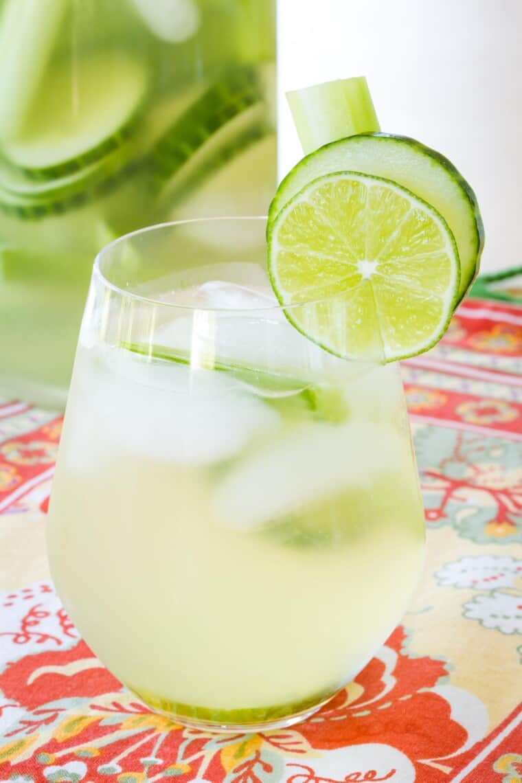 stemless wine glass filled with cucumber gimlet white sangria with more in a pitcher that has cucumber slices floating in it