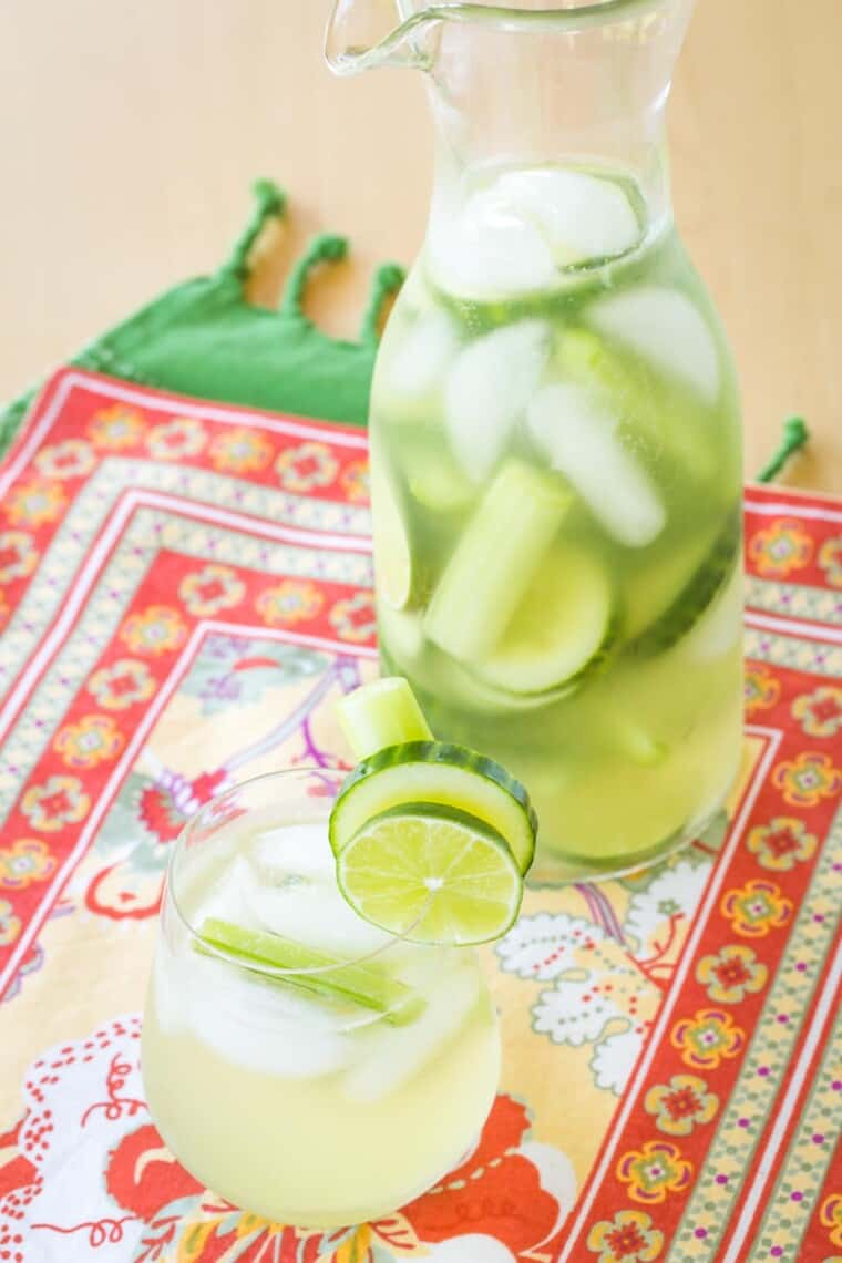 clear pitcher and a stemless wine glass filled with cucumber gimlet white sangria garnished with cucumber and lime slices and celery