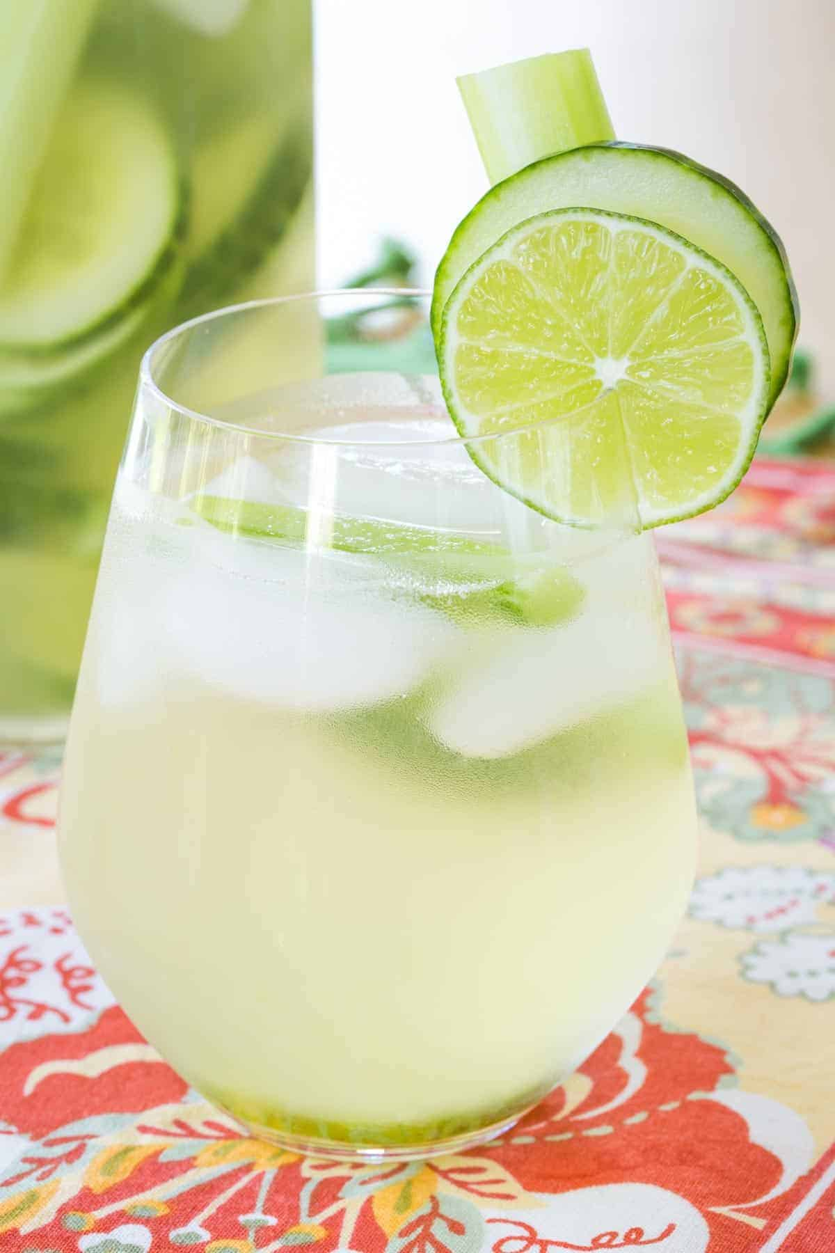 cucumber gimlet white sangria in a stemless wine glass garnished with cucumber and lime slices