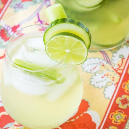 pitcher and glass of a white wine sangria on a bright floral placemat