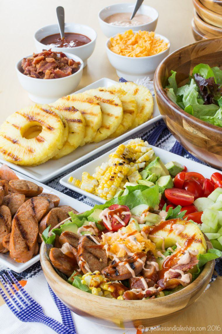 bowl of grilled sausage salad surrounded by bowls of salad toppings