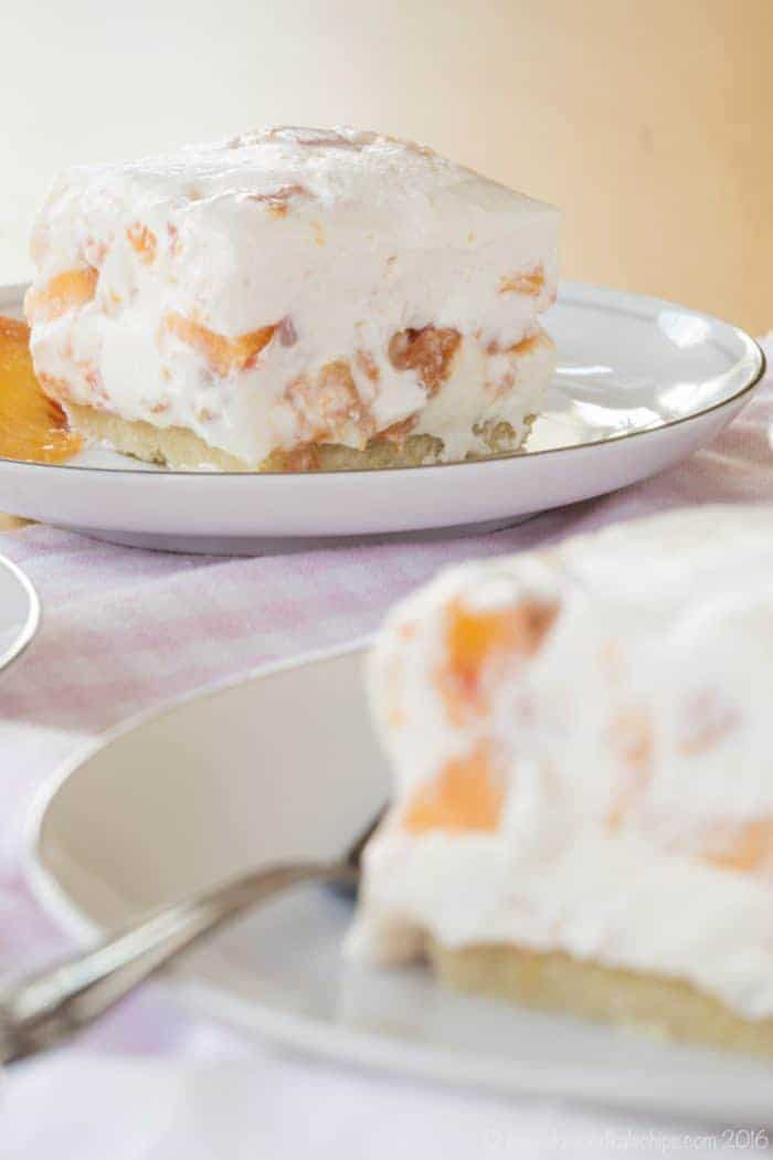Fresh Peach Cheesecake Squares with gluten free almond meal crust on white plates