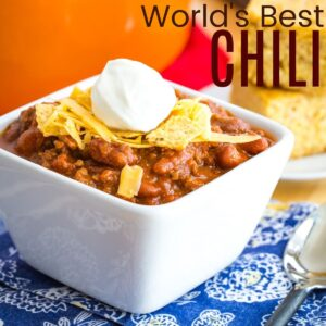 a bowl of the world's best chili with shredded cheese, crushed tortilla chips, and sour cream on top