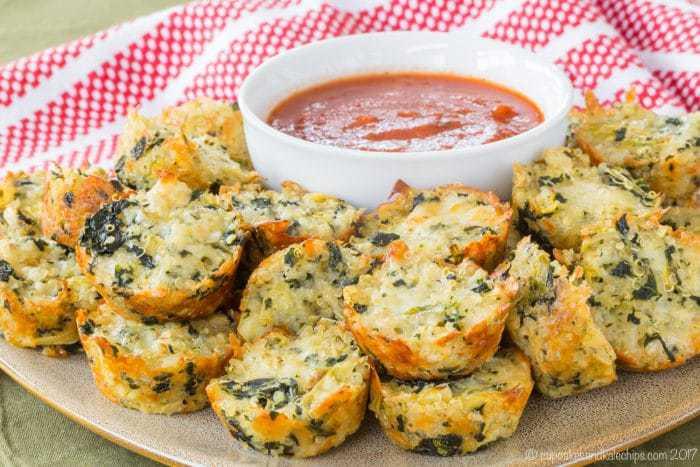 A platter of Quinoa Spinach Artichoke Bites with marinara sauce for dipping