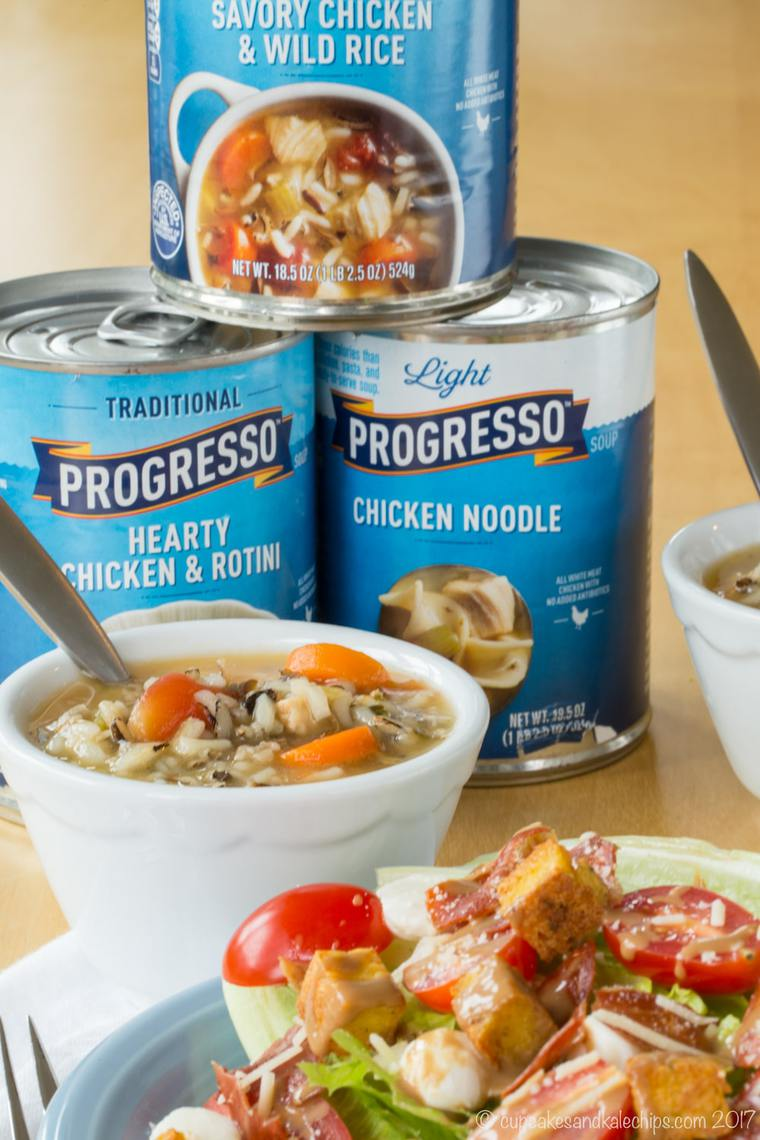 Cans of Progresso soup and a bowl of chicken wild rice soup served with a wedge salad