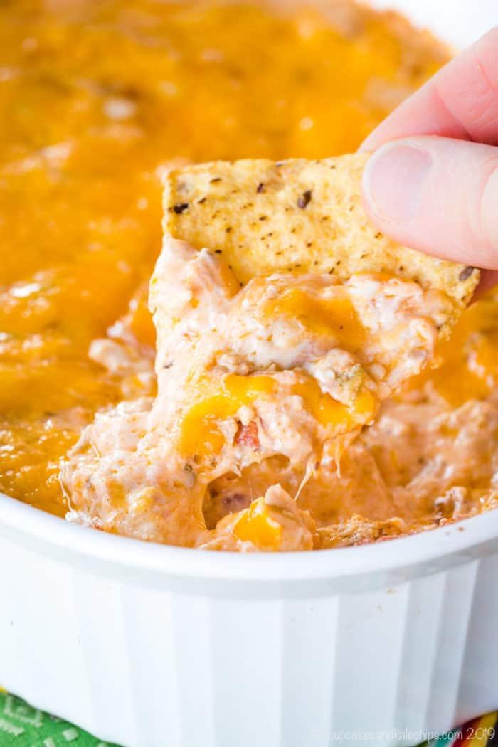 scooping up cheesy jambalaya dip with a tortilla chip
