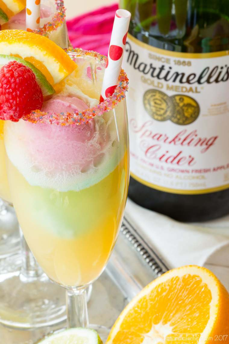 Sparkling cider in a champagne flute with small scoops of rainbow sherbet and a rainbow sugared rim