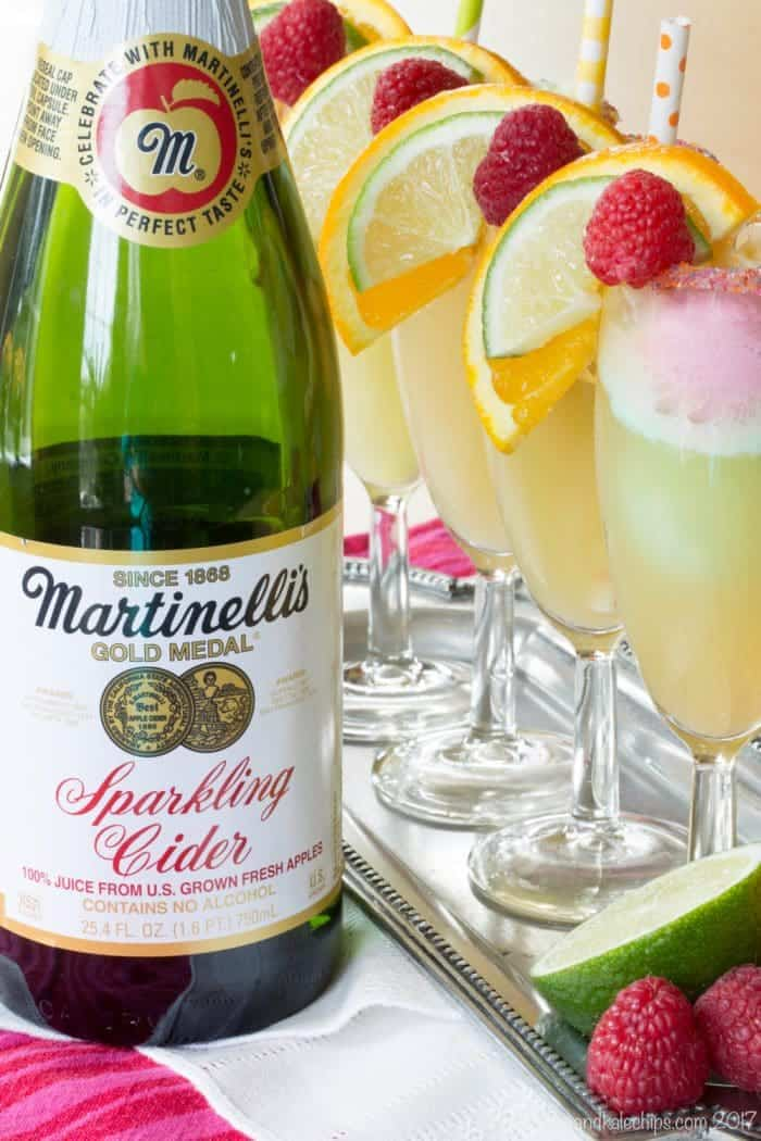 Bottle of Martinelli's Sparkling Cider next to a tray of floats in champagne glasses