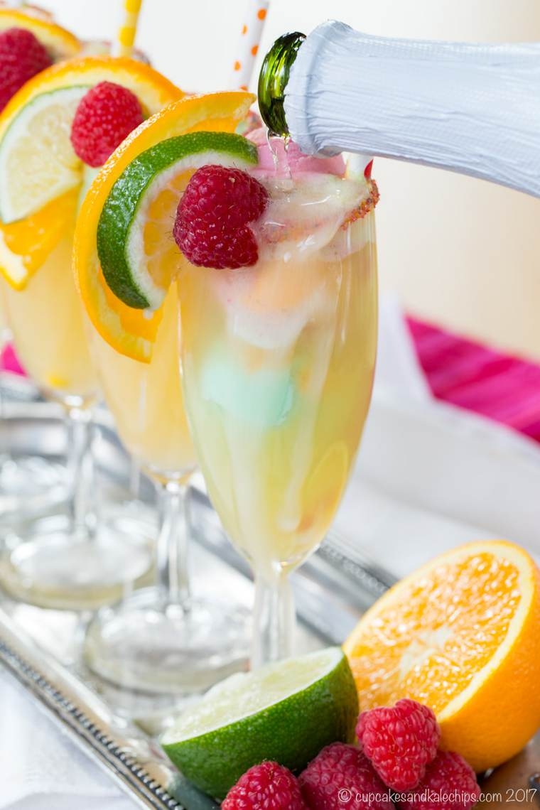 Pouring sparkling cider over small scoops of rainbow sherbet in a champagne flute
