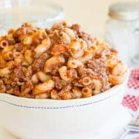 Classic Beefaroni in a white bowl with a red and white napkin