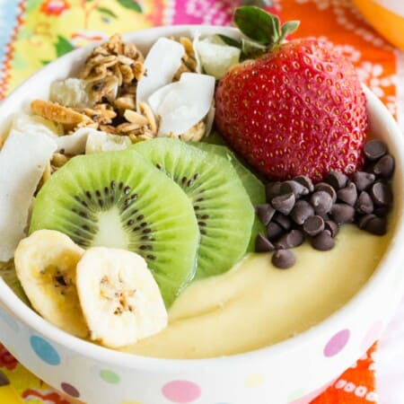 pink and white polka dot bowl filled with a thick pale yellow smoothie and fruit and granola on top