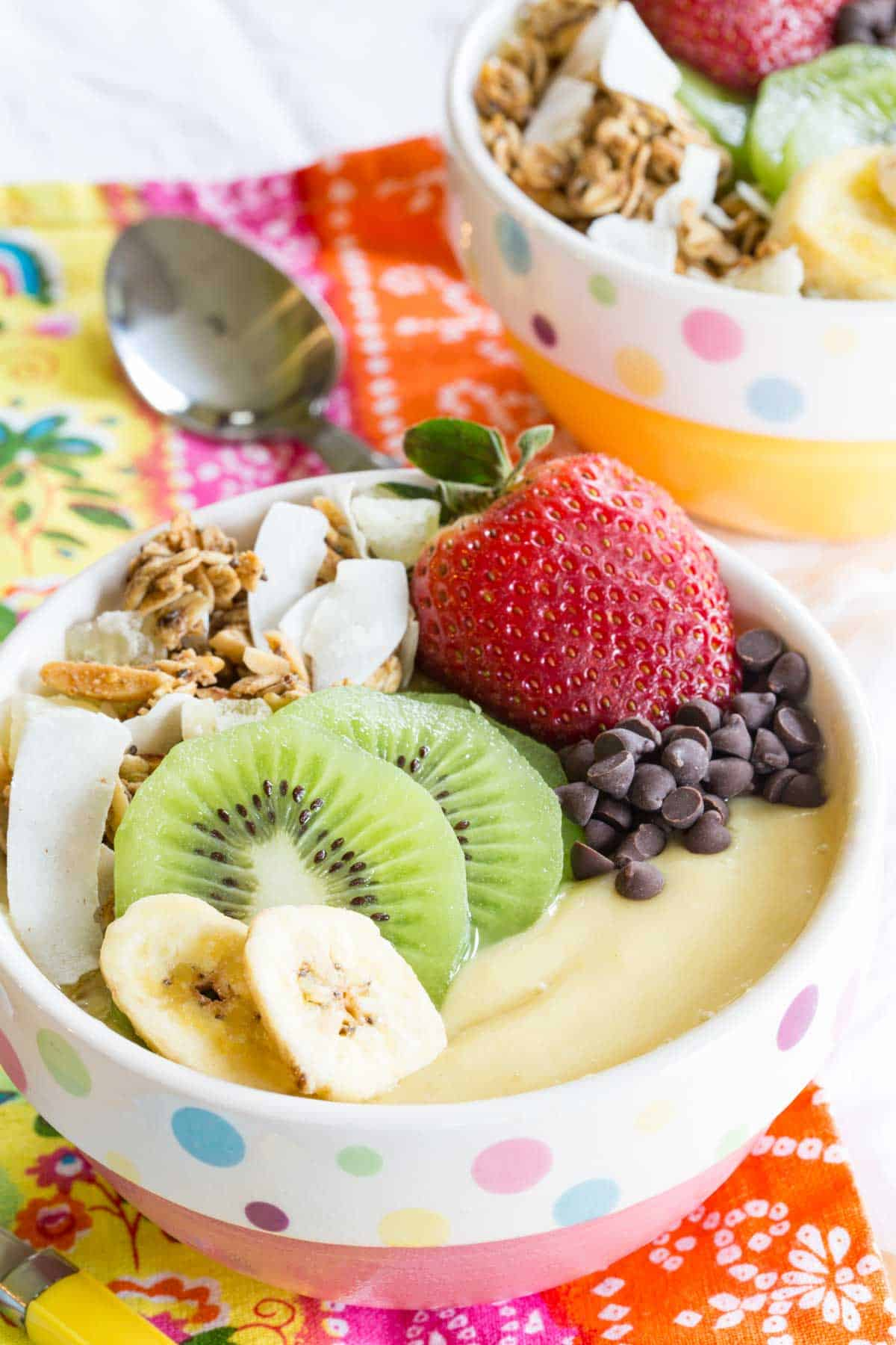 Tropical Smoothie Bowl topped with fresh fruit, chocolate chips, and granola
