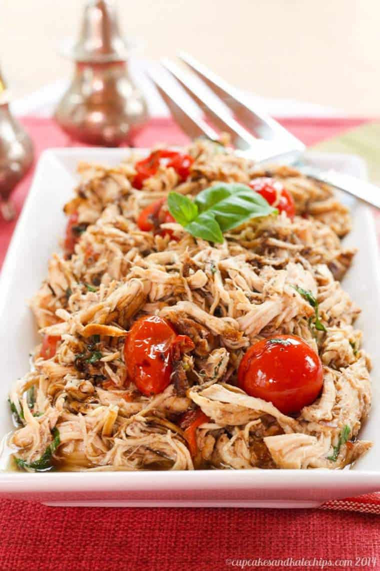 A rectangular white plate with Slow Cooker Balsamic Chicken with Tomatoes and Basil