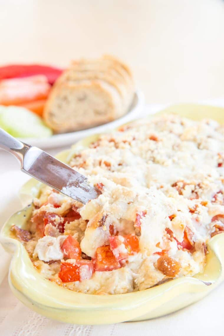 Hot cheesy dip filled with turkey, bacon, and tomatoes in a yellow casserole dish
