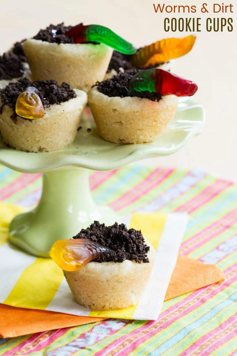 Worms and Dirt Cookie Cups - a kid-friendly sugar cookie cup recipe with only five ingredients. Sugar cookies are filled with chocolate ganache, Oreo dirt, and gummy worms. A perfect dessert to celebrate spring, Halloween, or just for fun. #cupcakesandkalechips #wormsanddirt #cookiecups #cookies #oreos #kidfriendly #cookingwithkids #bakingwithkids