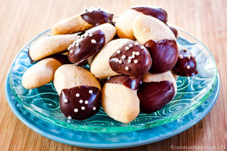 A plate stacked with Chocolate-Dipped Gluten Free Almond Crescents