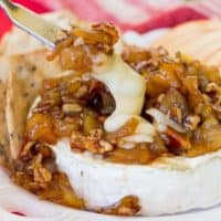 A cheese knife cuts into a melted wheel of Caramelized Apple Pecan Baked Brie