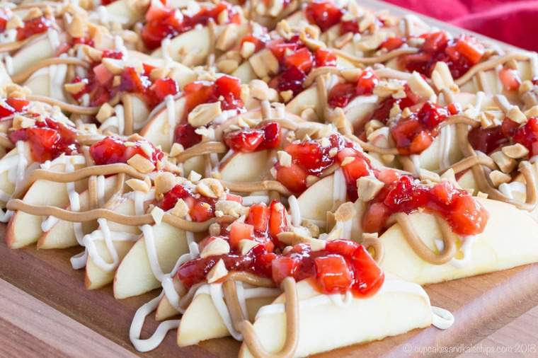 Sliced apples with peanut butter, strawberry salsa, and cheesecake drizzle on a platter