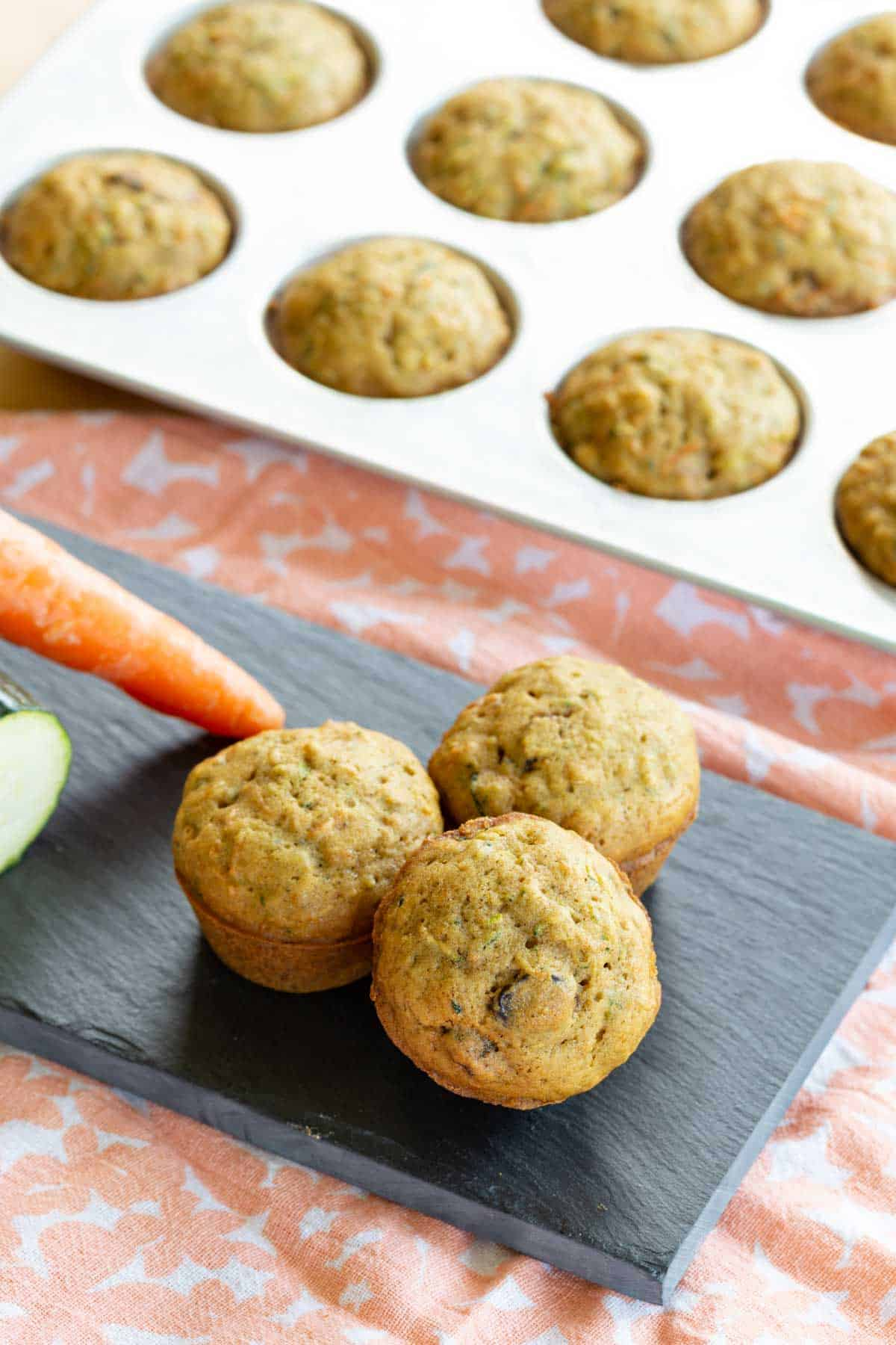 three gluten free mini muffins on a platter in front of a pan of more carrot zucchini muffins