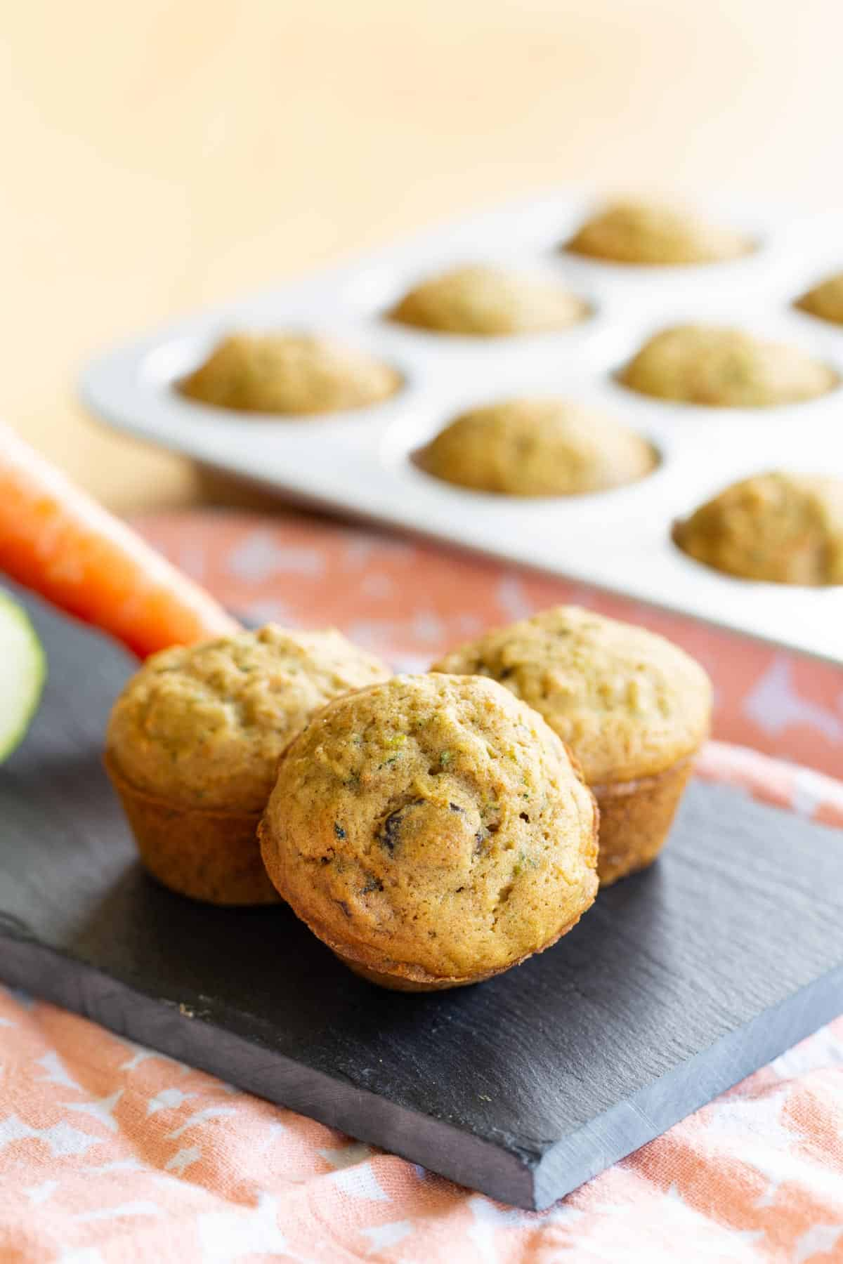 three gluten free carrot zucchini muffins on a platter with one leaning against the others