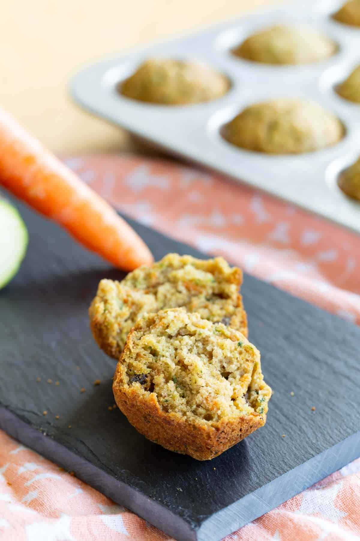 one gluten free mini muffin broken in half on a slate platter
