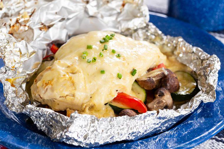 Cheesy Maple Dijon Chicken Foil Packets served in aluminum foil on a blue plate