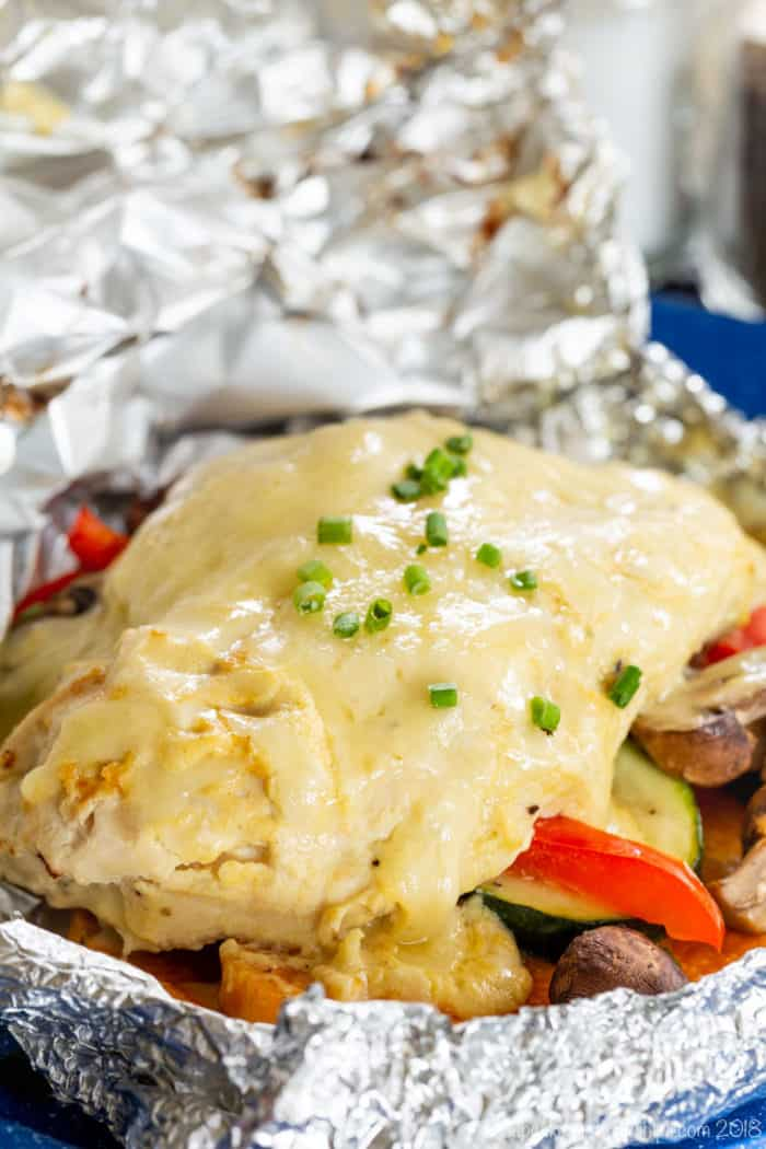 chicken and veggies in a foil pack with melted cheese on top