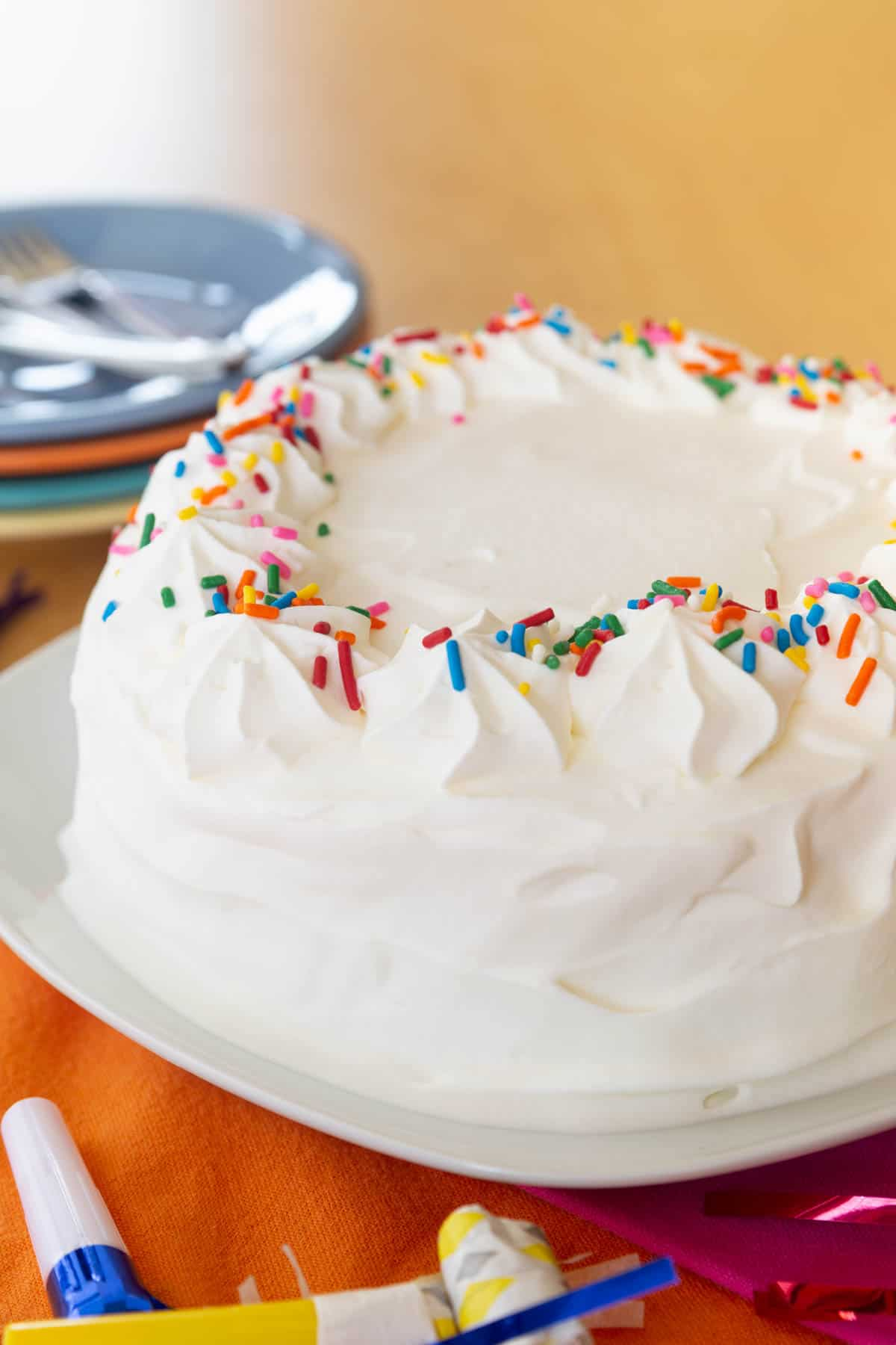 Whipped-cream covered cake on a white plate surrounded by plates and party horns
