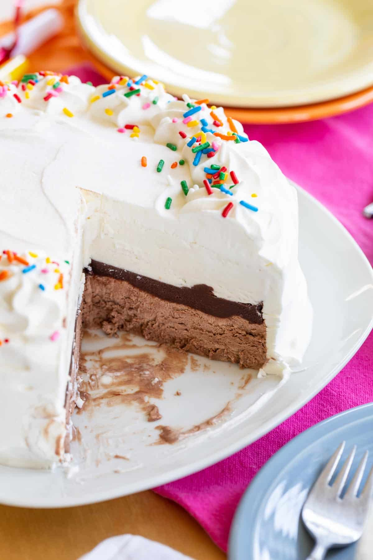 Homemade Ice Cream Cake on a white serving plate with a couple of slices removed