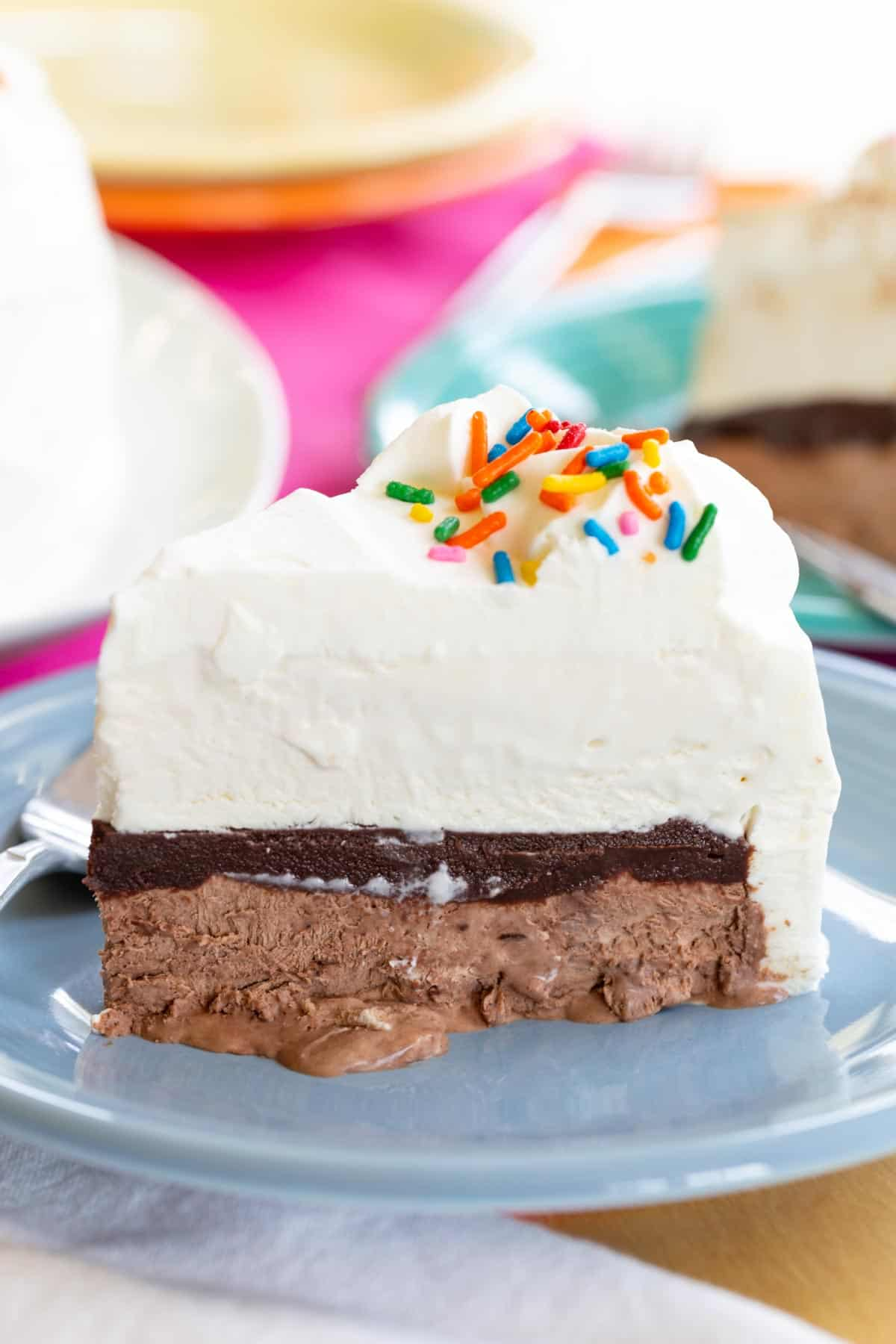 Ice cream cake with chocolate on the bottom, a later of fudge, then vanilla ice cream, and topped with whipped cream and sprinkles
