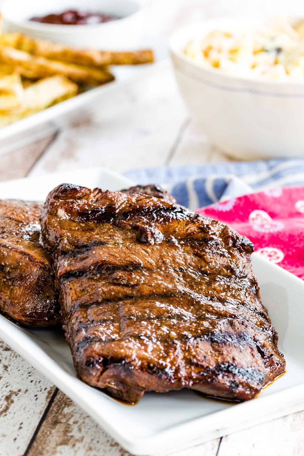two grilled steaks on a serving plate