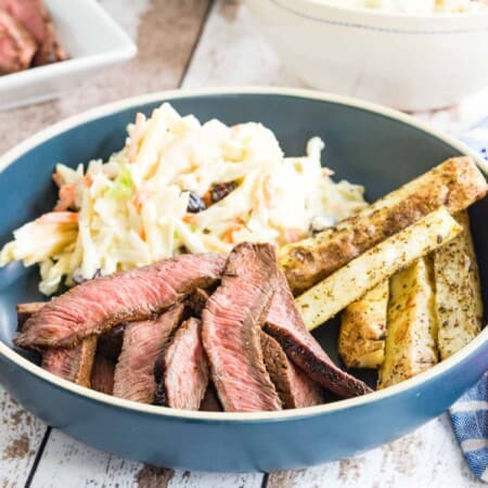 sliced flat iron steak, potatoes, and coleslae on a blue plate with cloth napkins and blue plastic utensils