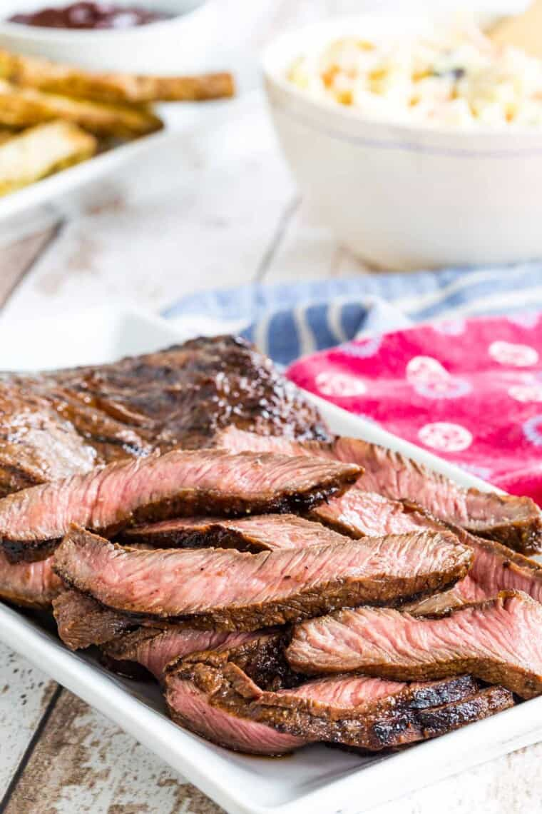sliced grilled flat iron steak on a white serving plate with bowls of side dishes behind it