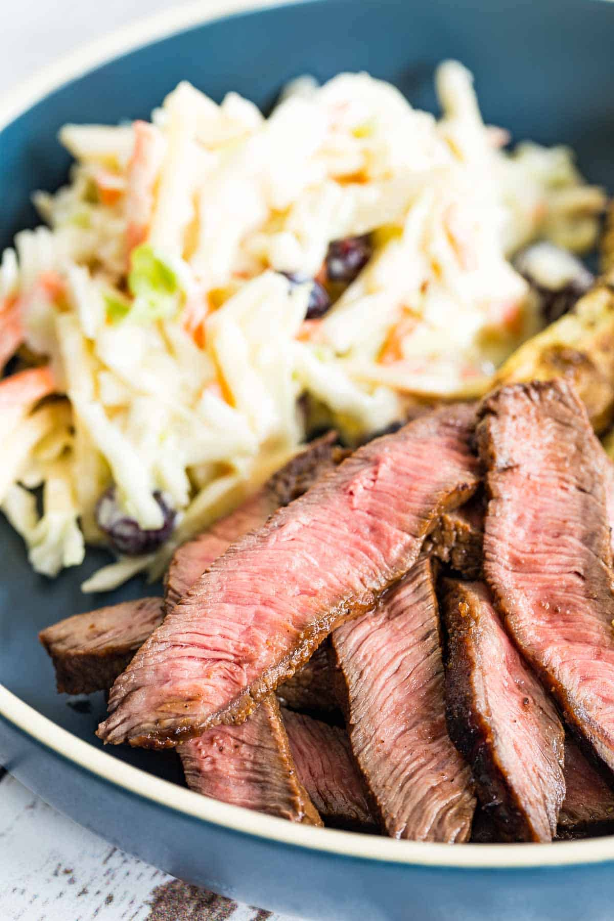 slices of steak on a blue plate with coleslaw
