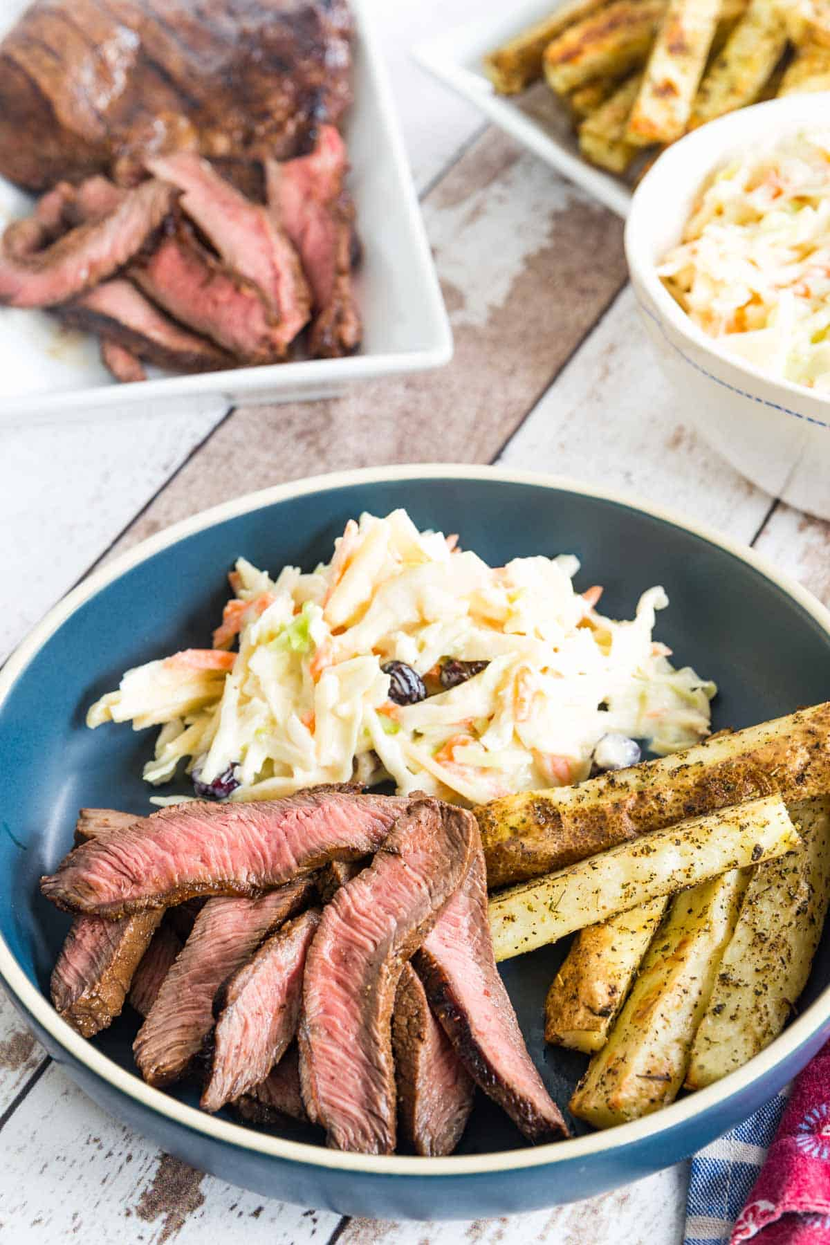 blue plate with sliced steak, baked french fries, and coleslaw