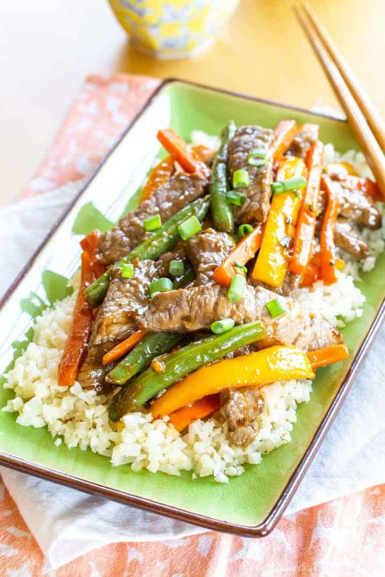 Gluten Free Steak Stir Fry with Veggies and cauliflower rice on a green rectangular plate