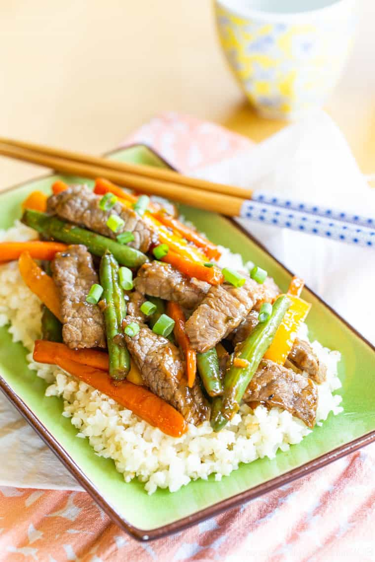 Gluten Free Beef Stir Fry with bright colored veggies on a plate with chopsticks