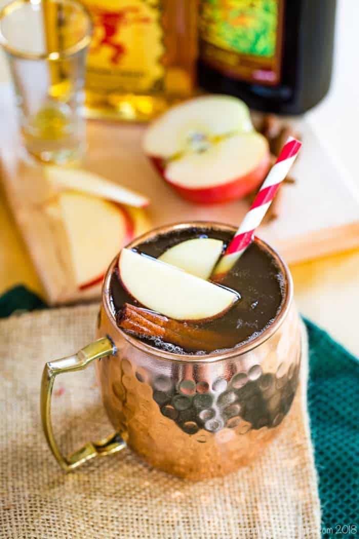 Spiced Apple Cider Moscow Mule Cocktail with apple slices and cinnamon sticks