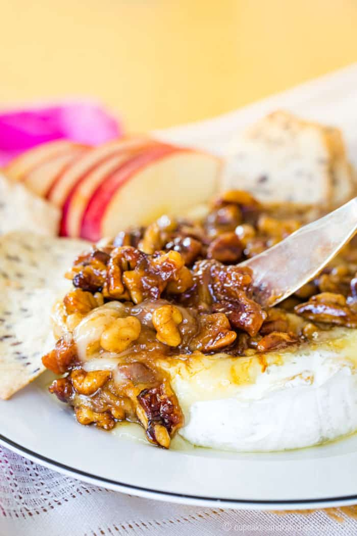 Using a knife to scoop up Honey Glazed nuts and melty baked Brie