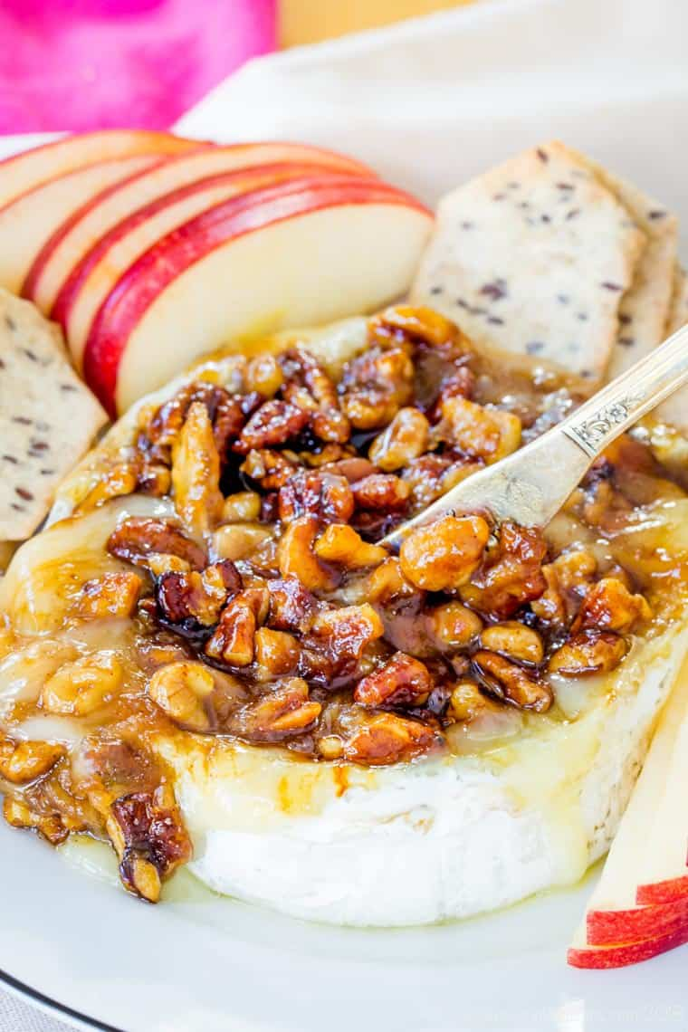 Scooping up Honey Nut Baked Brie cheese with a spreader