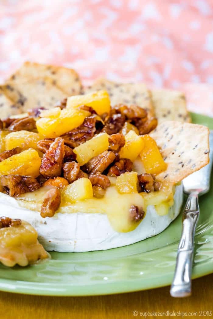 Baked brie on a green plate with a serving knife, topped with pineapple and pecans