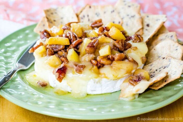 Pineapple Pecan Baked Brie Cheese on a light green plate surrounded by crackers