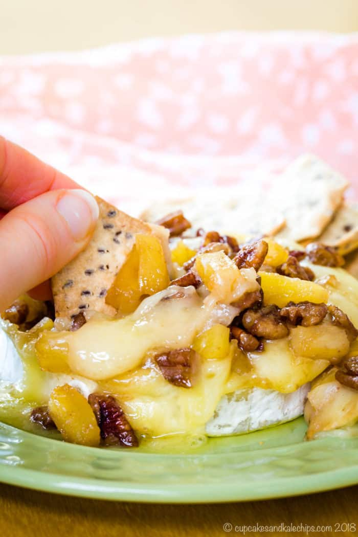 Pineapple Pecan Baked Brie being scooped with a cracker