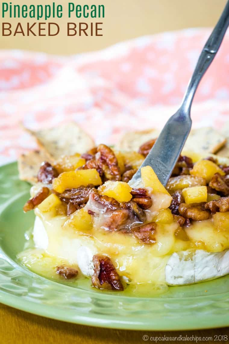 Baked brie on a green plate topped with pineapple and pecans