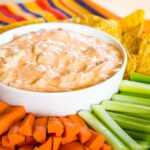 Bacon Blue Cheese Buffalo Dip on a platter with tortilla chips, carrots, and celery