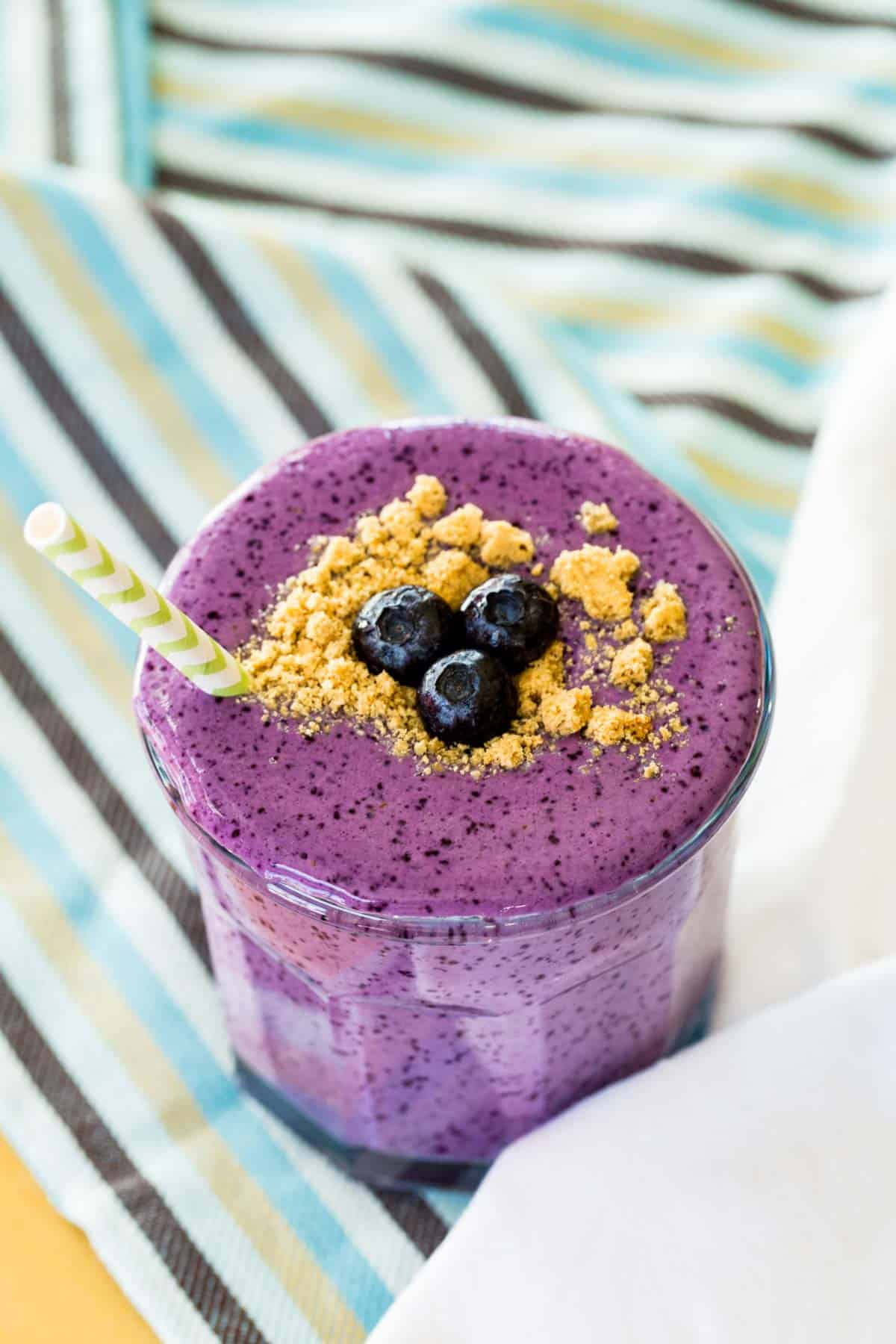 Blueberry Cheesecake Smoothie in a glass on a blue and brown striped napkin
