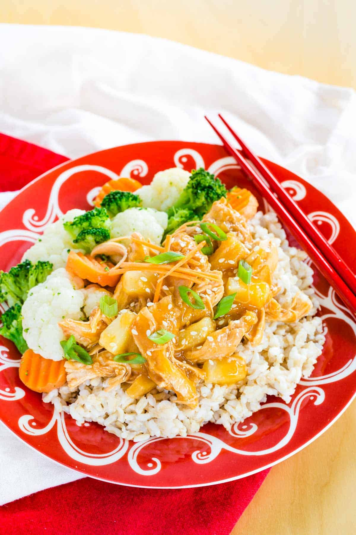 Instant Pot Pineapple Teriyaki Chicken on a plate with red chopsticks set on top of red and white cloth napkins