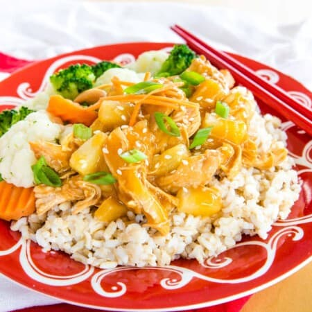 Pineapple Teriyaki Chicken Over rice on a red and white plate with red chopsticks