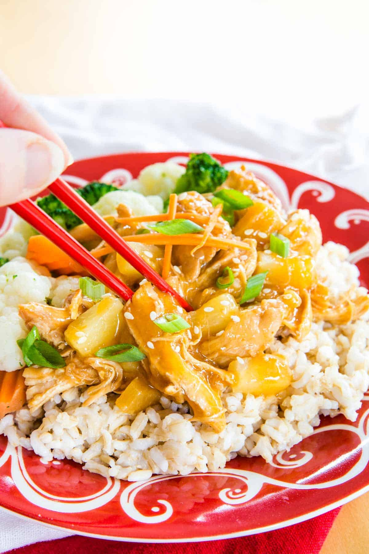 hand using red chopsticks to pick up pineapple teriyaki chicken served over brown rice