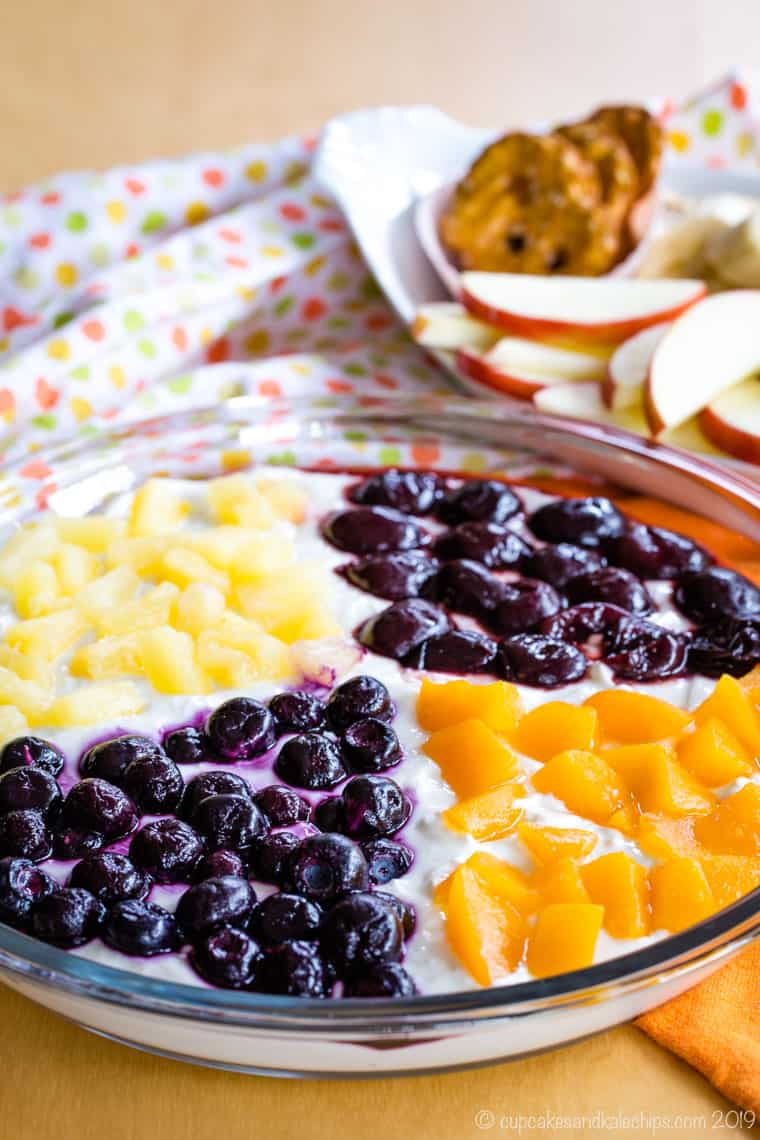 Greek Yogurt Cheesecake Fruit Dip with a different kind of Dole fruit topping on each quarter